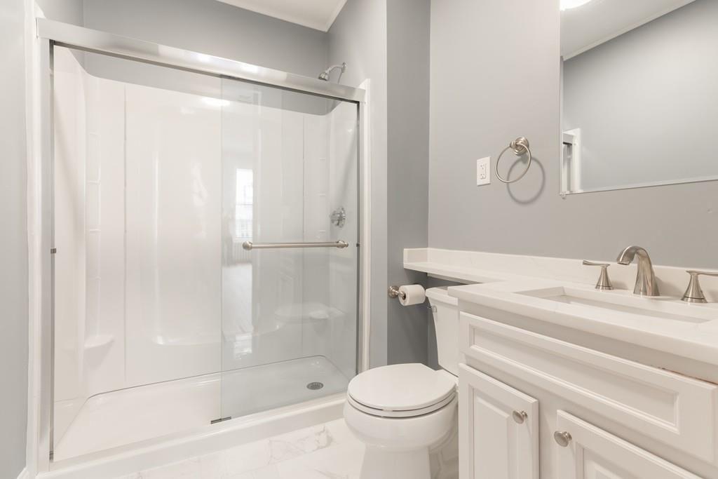 A bathroom with a sliding-glass door on the tub.