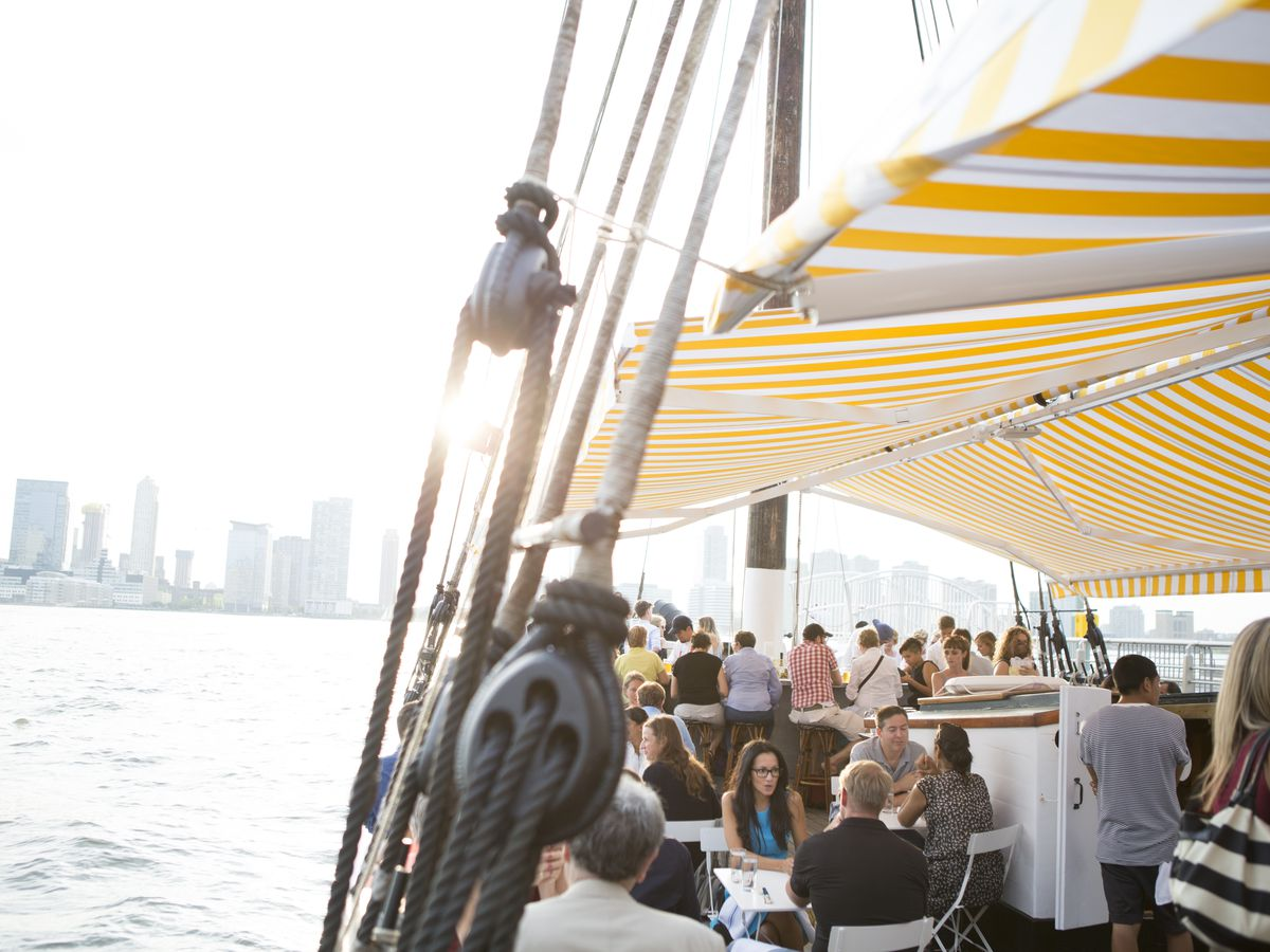 Dozens of people are seated at tables and chairs on the hull of a boat