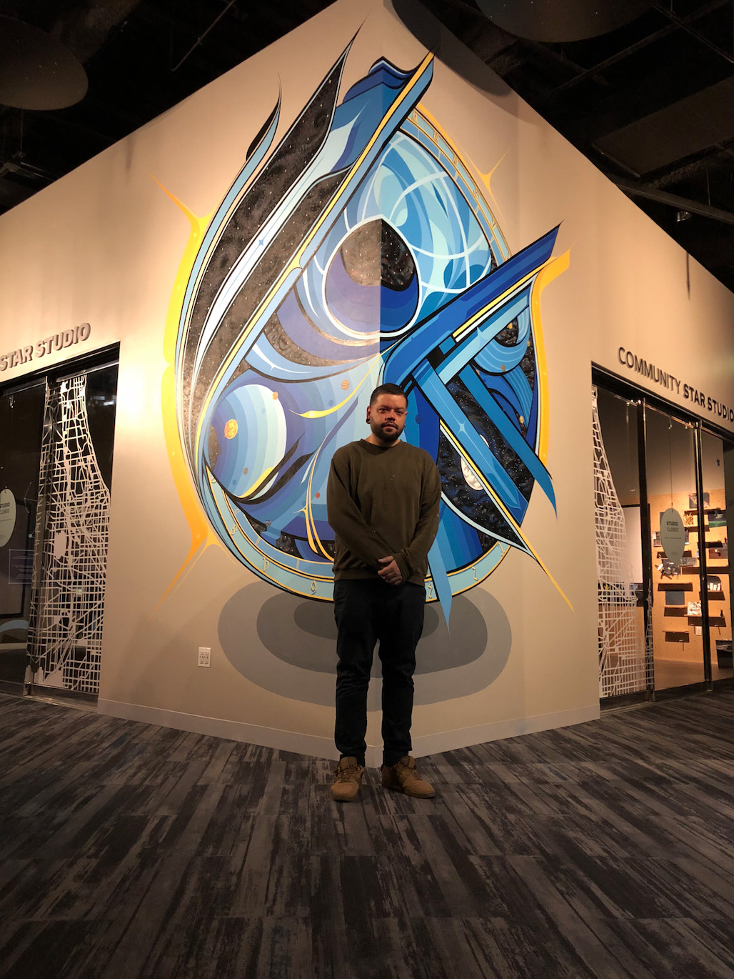 """Miguel Del Real in front of his """"Star Gate"""" mural at the Adler Planetarium."""