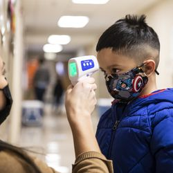 A preschool student gets his temperature checked as he walks into Dawes Elementary School at 3810 W. 81st Pl. on the Southwest Side, Monday morning, Jan. 11, 2021.