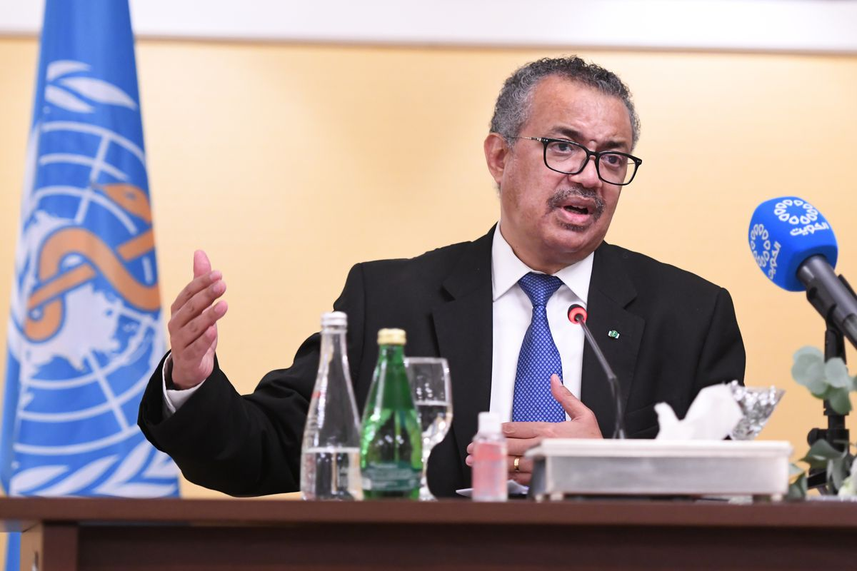 WHO Director-General Tedros Adhanom Ghebreyesus in a suit and tie speaking behind a podium desk with his hands in motion.