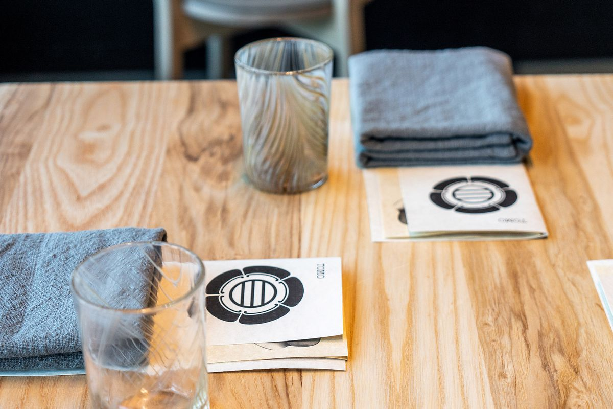 """A light wood table, with napkins and glasses, alongside menus that say """"Tomo"""" with the restaurant's logo."""