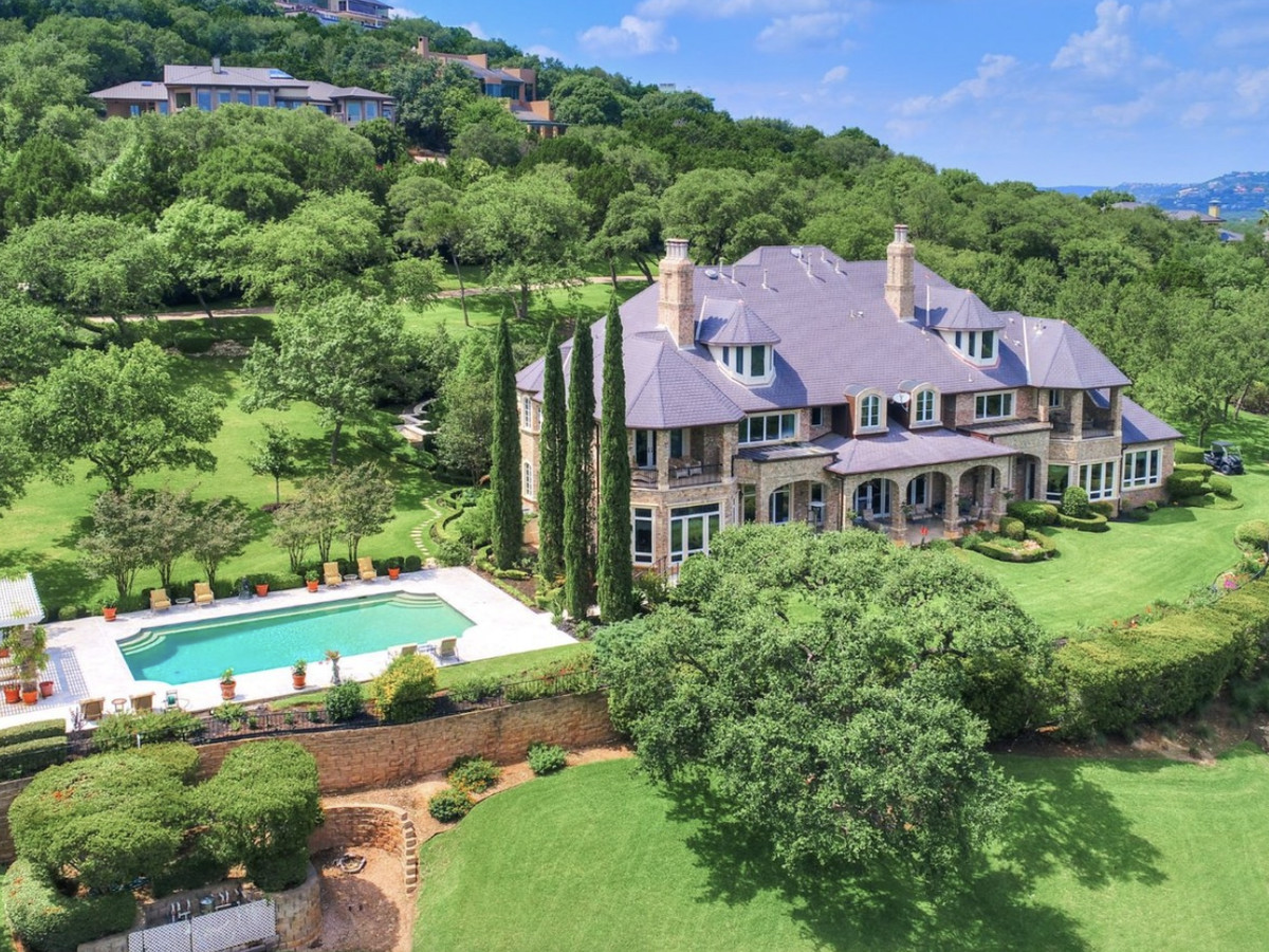 Aerial shot of a large, multistoried brick house with steep roof lines and two chimneys. It's on a tree-covered hillside and has manicured, terraced lawns. There's a large swimming pool to the left of the house, separated by tall Italian cypresses.