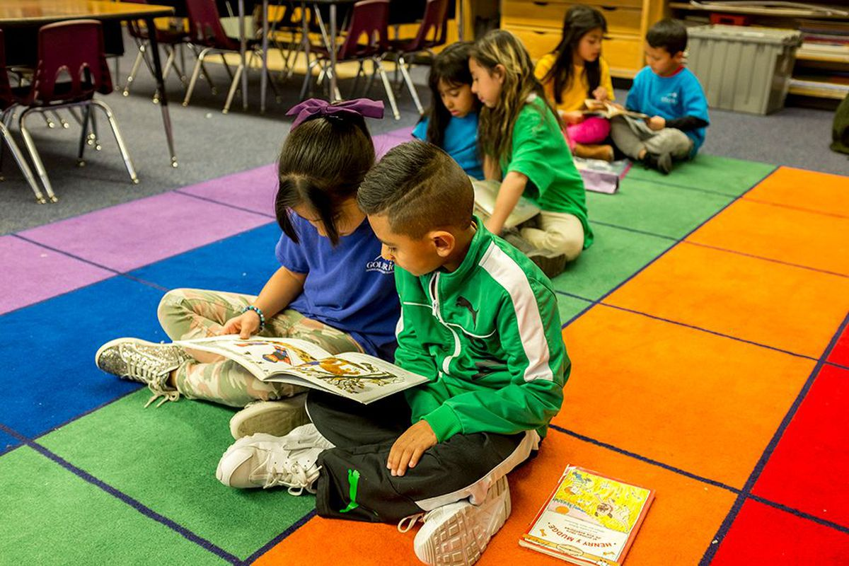 Three pairs of students read books together while sitting on a multi-colored square rug.