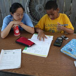 In this Tuesday, Oct. 11, 2010 photo, Monica Zheng, an 18-year-old volunteer and student at the University of Chicago, tutors Joshua Williams, 11, as he does his homework outside the Blackstone Bicycle Works in Chicago. The facility has an after-school program where young people can earn a free bike by working at the shop for 25 hours. Zheng also asked if she could earn a bike.