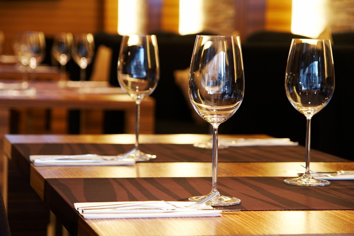 An empty table at a restaurant with wine glasses and menus