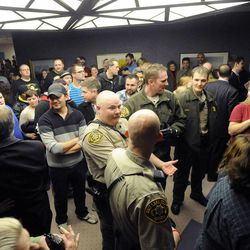 Salt Lake County sheriff's deputies stand in line to mark the end of the line for those whose marriage licenses will be processed for the day as the line continues behind them after a federal judge ruled that Amendment 3, Utah's same-sex marriage ban, is unconstitutional on Friday, Dec. 20, 2013.