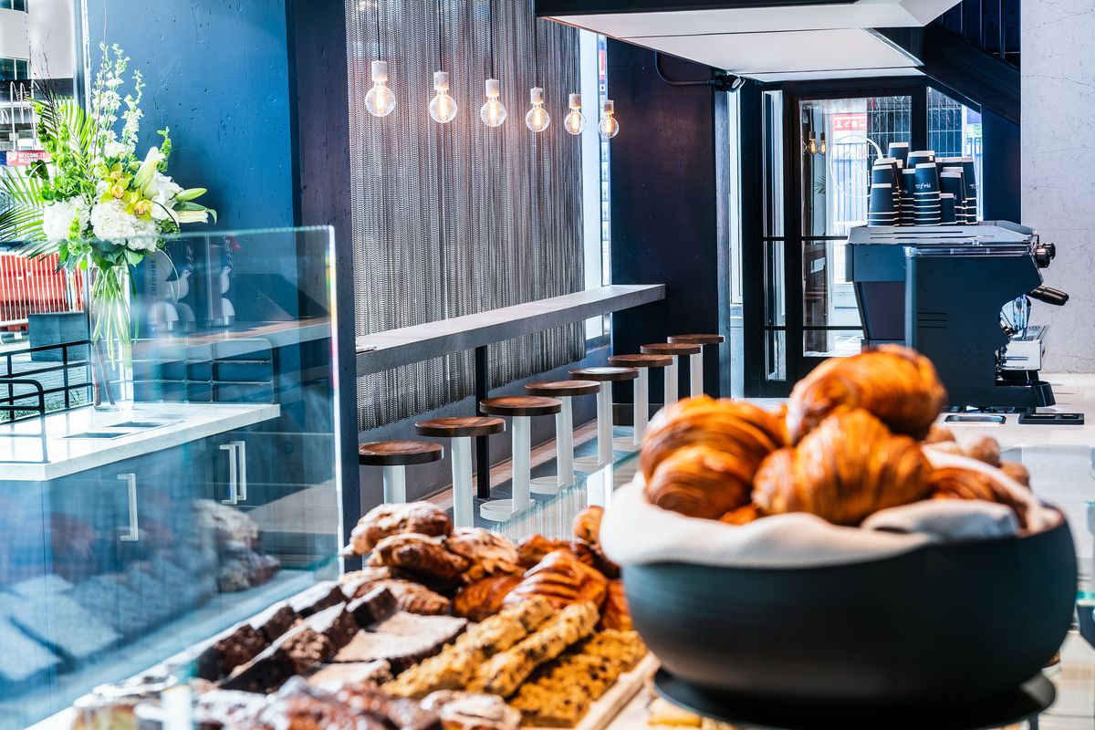 An interior shot of a bakery with a long bar and espresso machine. In the foreground is a bowl of croissants and a platter of pastries and cookies.