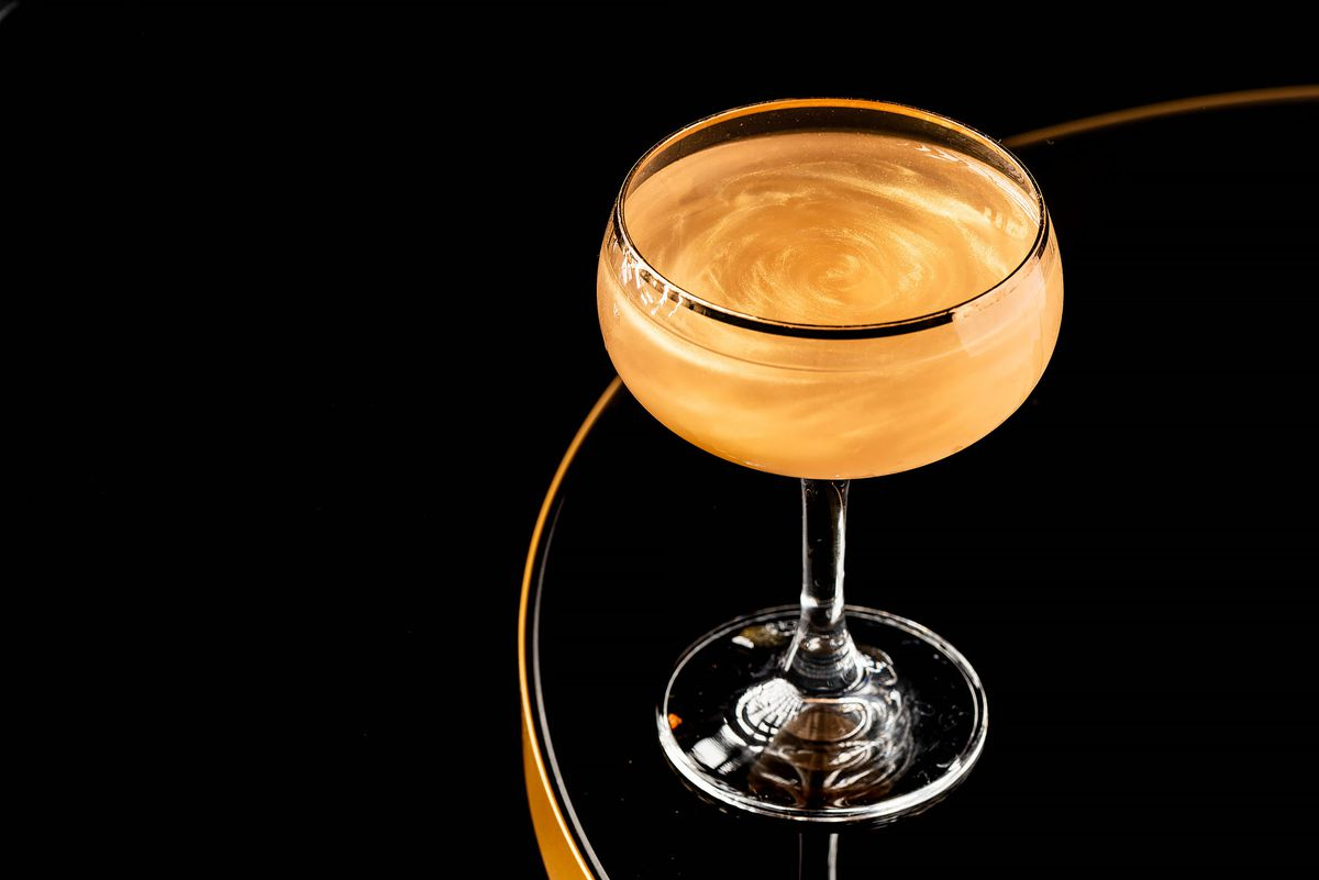 Flame of Love cocktail with vodka, gin, fino sherry, and gold dust in a gold rimmed coupe glass.
