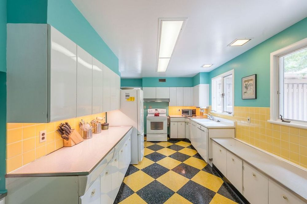 A midcentury modern kitchen with a yellow and black tiled floor, bright blue walls, glossy light blue cabinetry, and yellow wall tiles above the countertops.