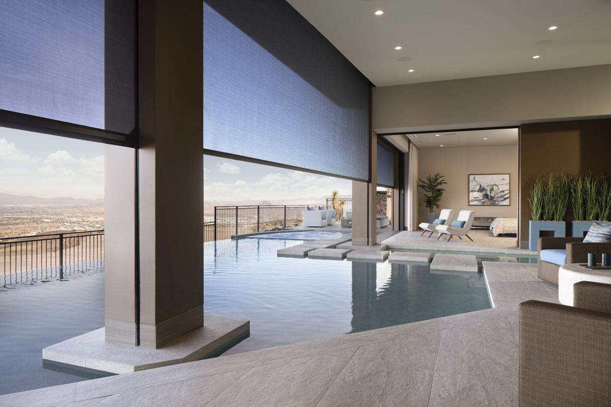 A large pool that wanders inside to the living room is shown with seats and couches, with the desert landscape in the background.
