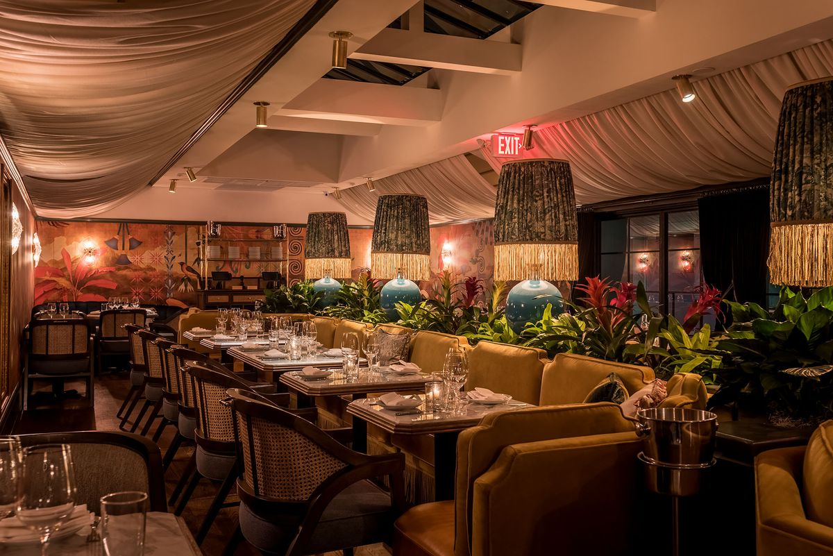 Tall lamps run down the center of a seating arrangement inside a colorful new restaurant.