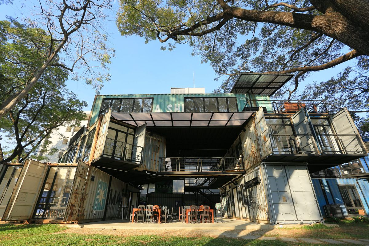 Shipping container building surrounded by trees