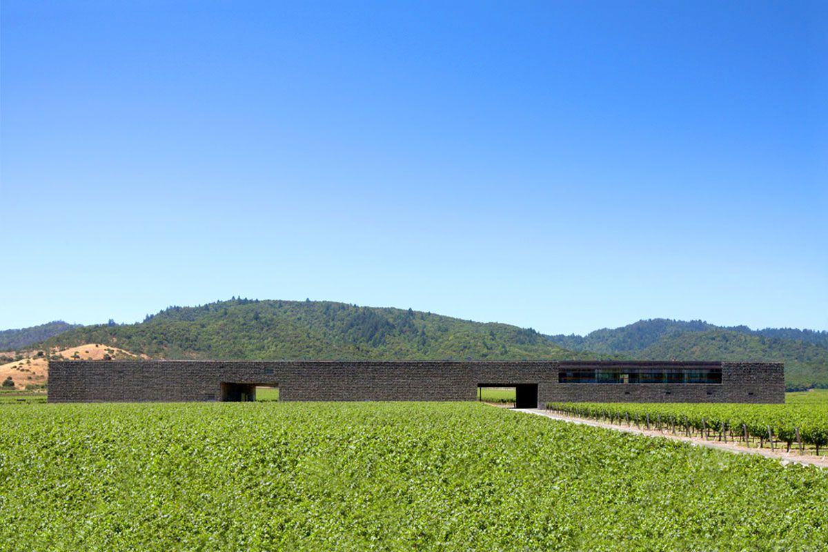 The exterior of Dominus Estate in California. The building is dark grey brick and low to the ground. There are vineyards in the foreground.