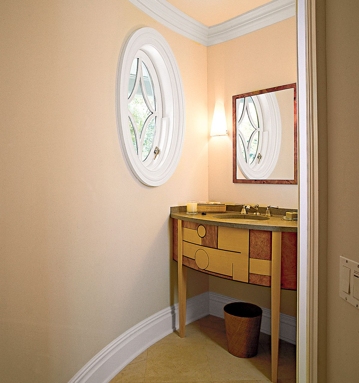 <p><strong>Throwing a Curve</strong><br> Architect Chris DiSunno commissioned a custom limestone-topped maple vanity to echo the curved wall in this under-the-stairs powder room. The commode sits at the opposite end of the room where the ceiling drops to 5 feet.</p>