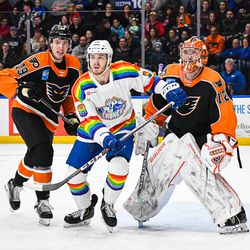 Syracuse Crunch Taylor Raddysh (18) setting up in between Lehigh Valley Phantoms Isaac Ratcliffe (19) and goalie Kirill Ustimenko (72) in American Hockey League (AHL) action at the Upstate Medical University Arena in Syracuse, New York on Saturday, February 22, 2020. Syracuse won 2-1.