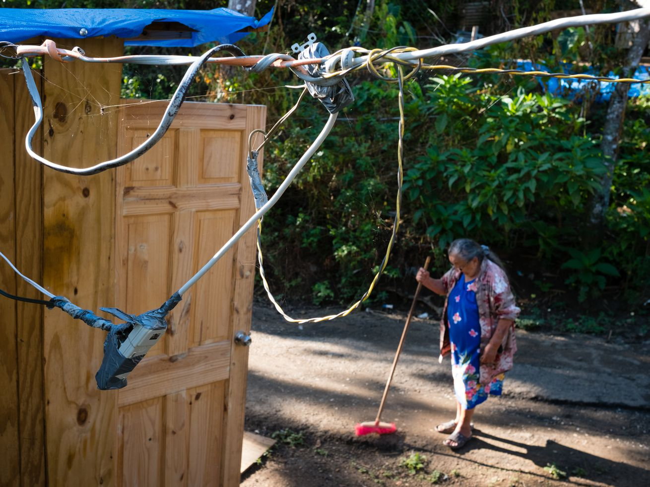 After her home was completely destroyed by Hurricane Maria, Petra Gonzalez, 85, sweeps the walkway of her temporary wooden shack where a bundle of wires supply the electricity on August 27, 2018.