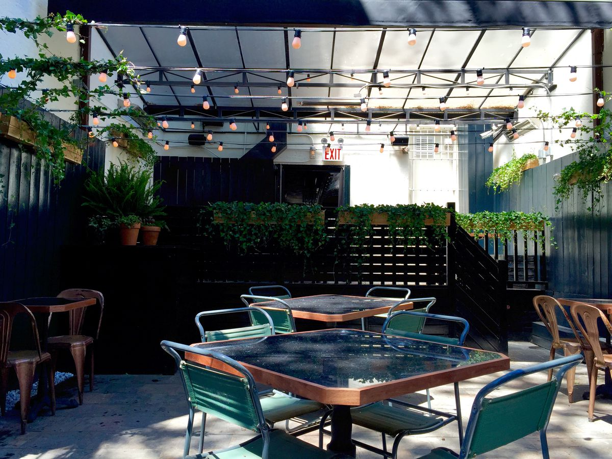 A backyard patio with tables, chairs, and market lights overhead