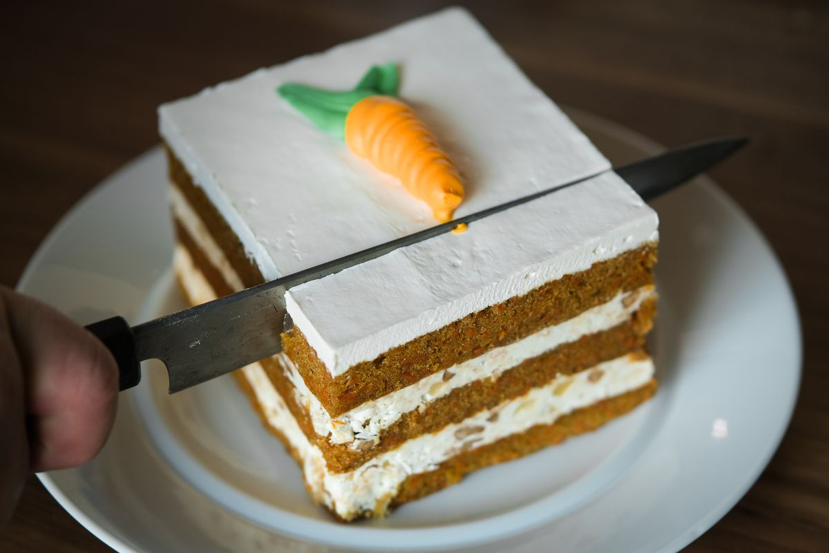 A square slice of triple-tiered carrot cake with a single frosting carrot on top.