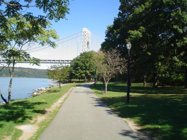 A park path. The path has grass on both sides and trees. In the distance is a bridge. There is a body of water to the left of the path.