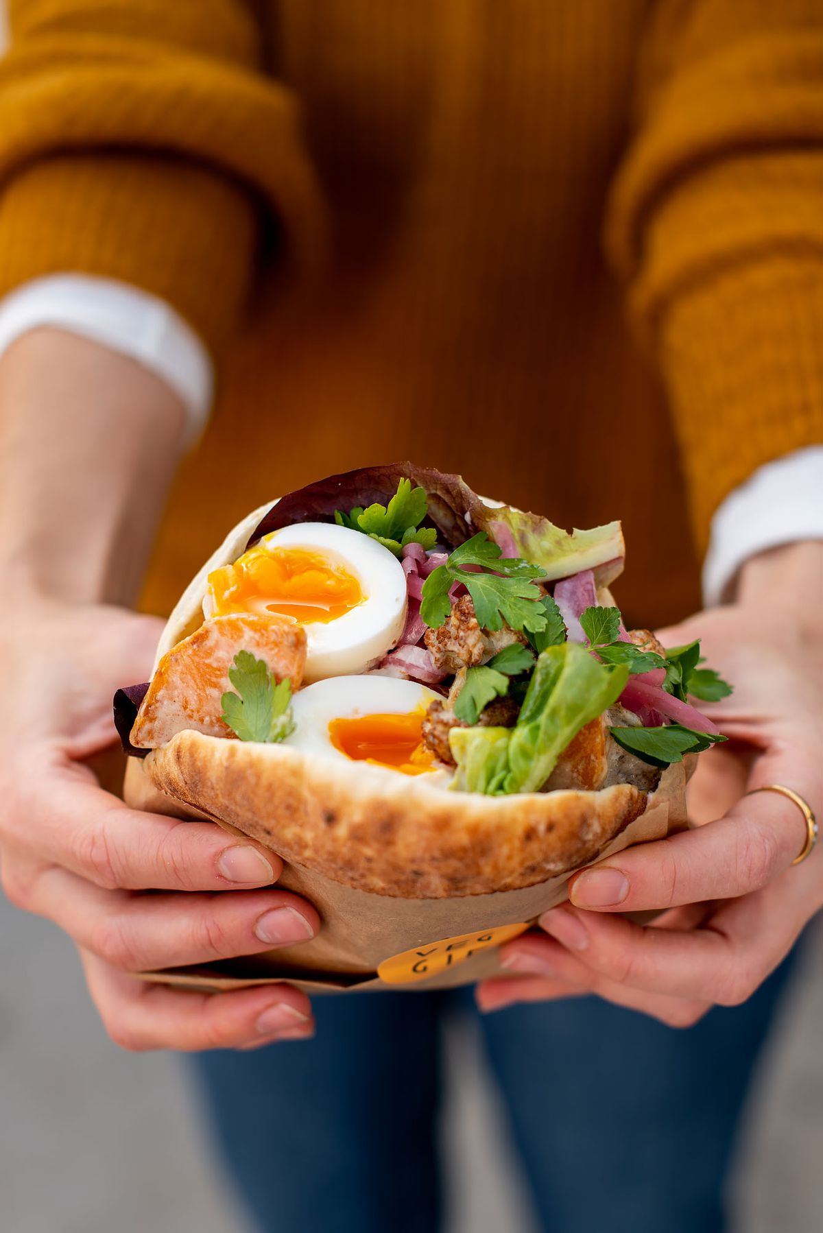 An open pita sandwich with soft eggs and greens inside.