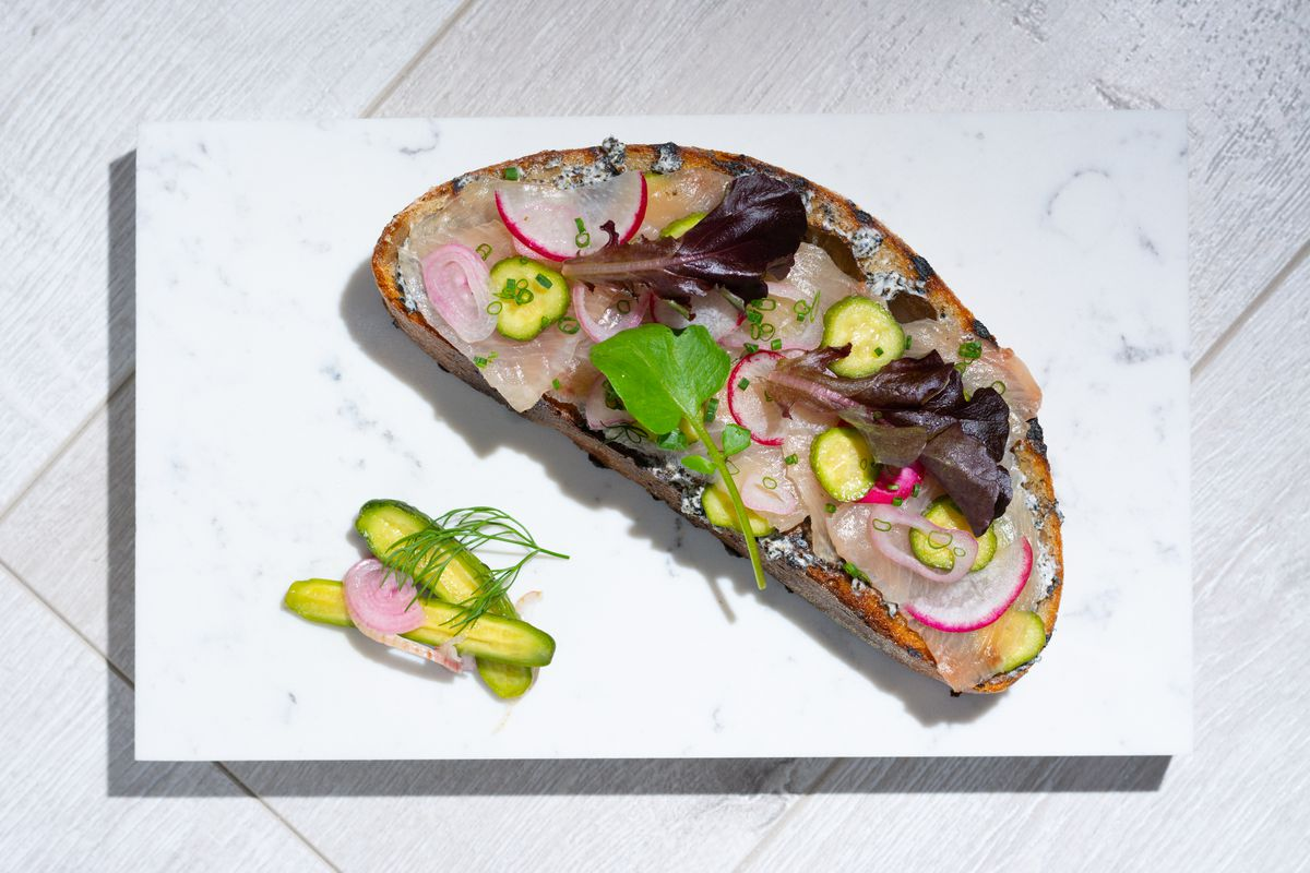 slice of bread with colorful vegetables and fish