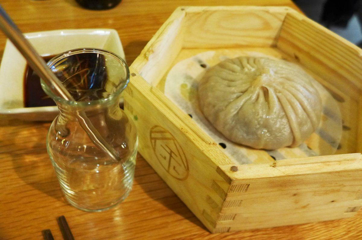 In a bamboo steamer see a single giant round dumpling, with a metal straw on the side...