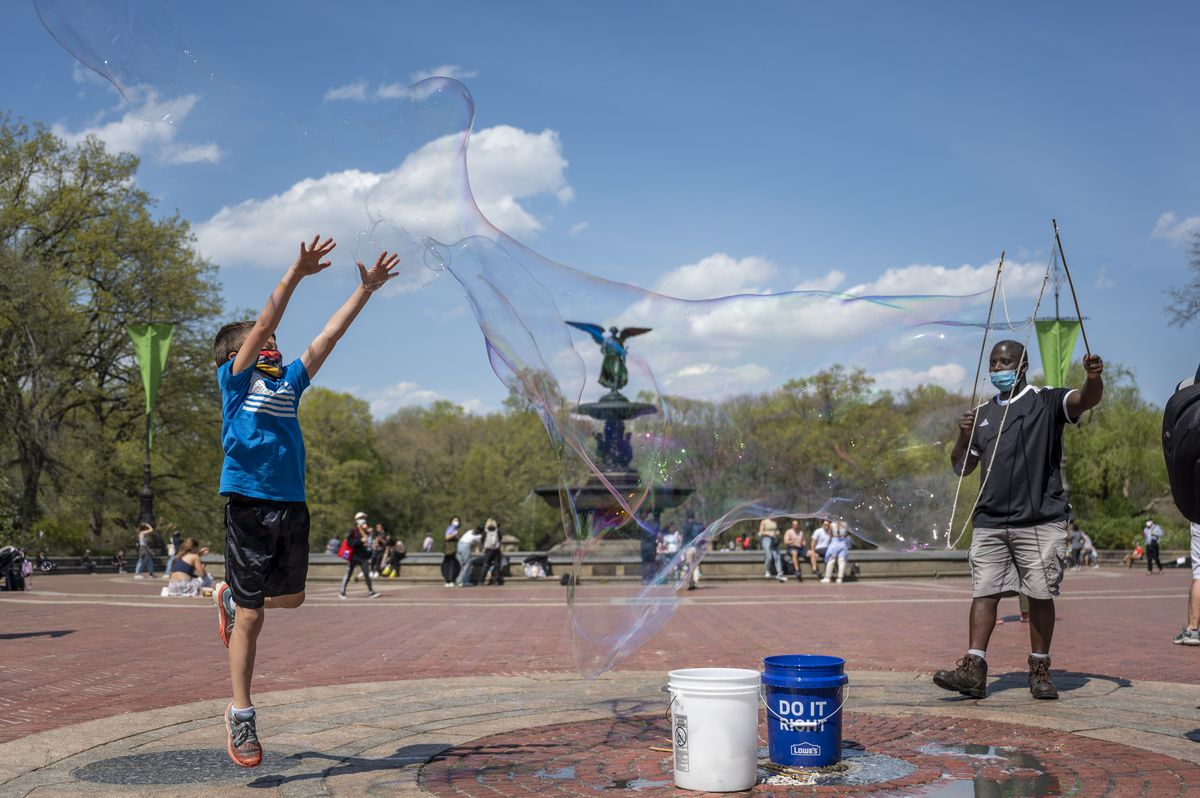 A child jumps to pop a large and streaking soap bubble near Bethesda Fountain.