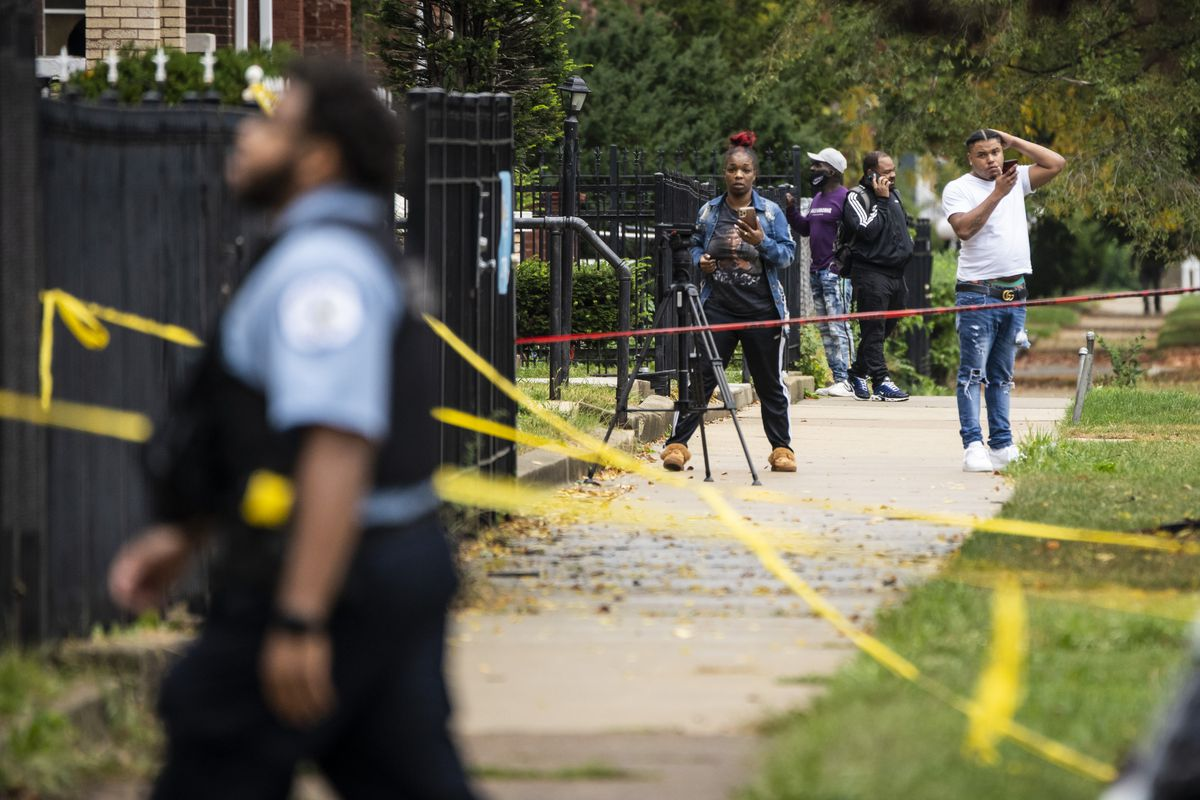 Neighbors watch as Chicago Police investigate inside an apartment in the 7700 block of South Carpenter Street after an officer shot and killed a man while answering a call of a domestic disturbance in the Gresham building on the South Side, Monday morning, Oct. 4, 2021.