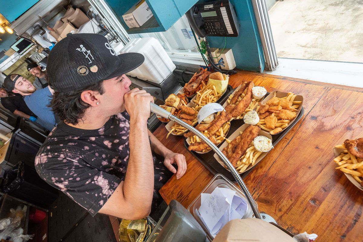 A man calls out a large fried fish order over a microphone.