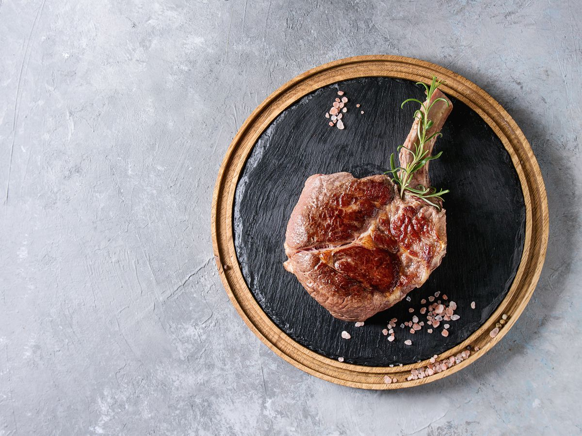 Grilled black angus beef tomahawk steak on bone served with salt, pepper and rosemary on round wooden slate cutting board over grey texture background