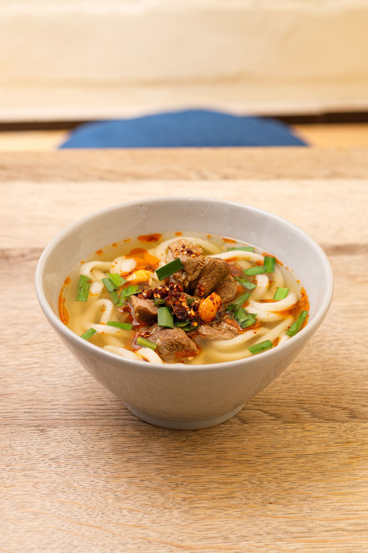 A bowl of udon noodles with beef shin and chilli oil, sitting on a light wood table