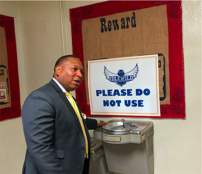 Superintendent Joris Ray shows reporters one of the water fountains that was shut off at Idlewild Elementary after test results showed high levels of lead.