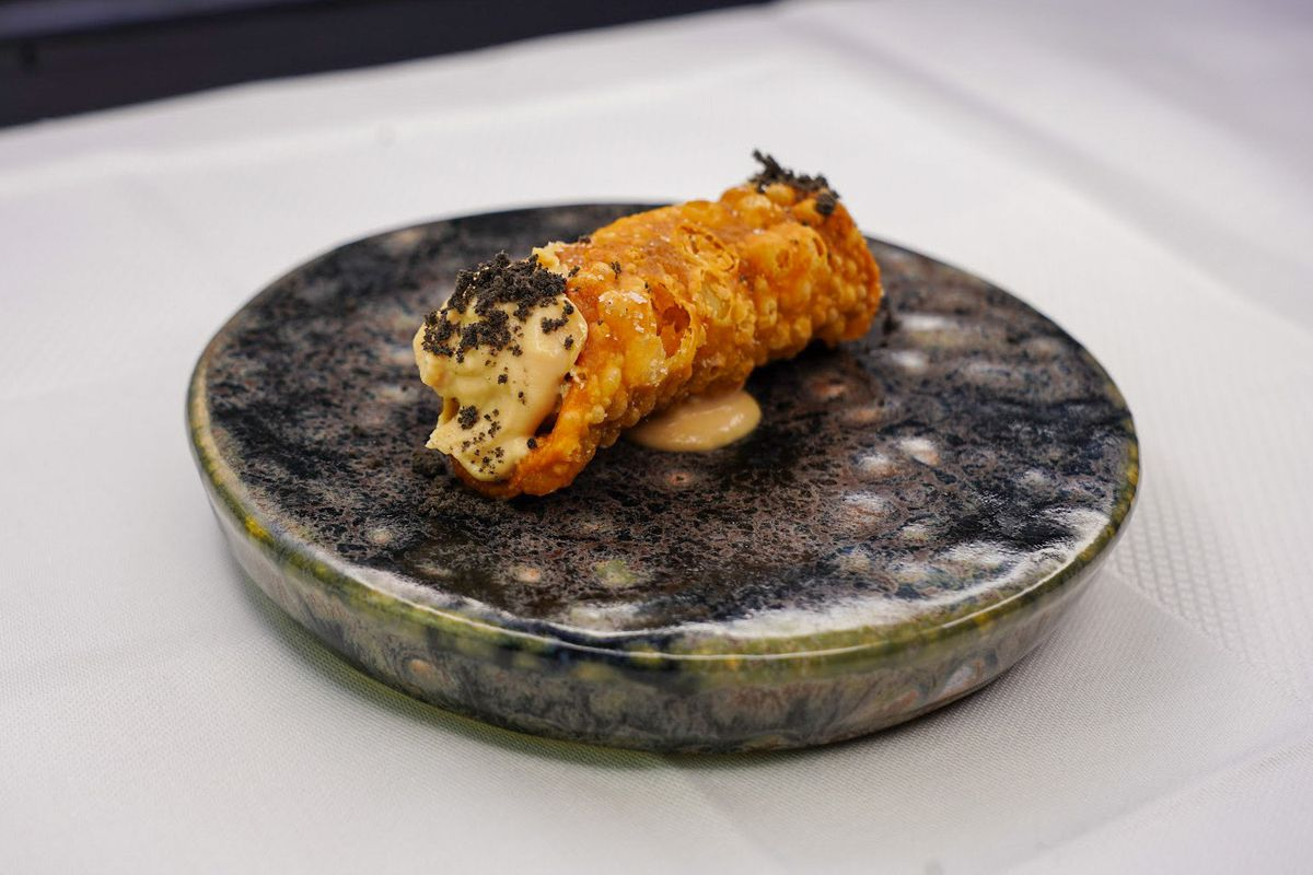 A fried pastry stuffed with foie gras rests on a black ceramic plate