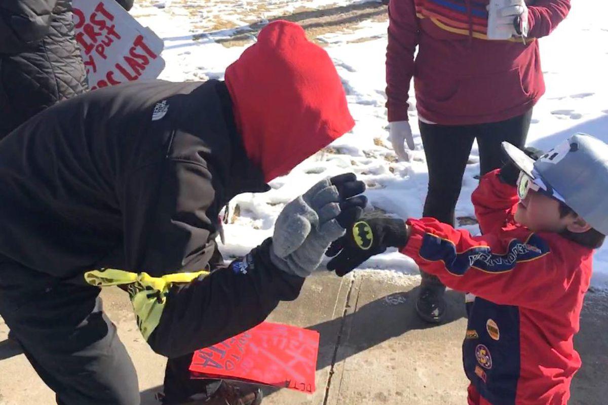 A Denver preschooler gives a striker a high five while walking the picket line with his mother, a Denver teacher.