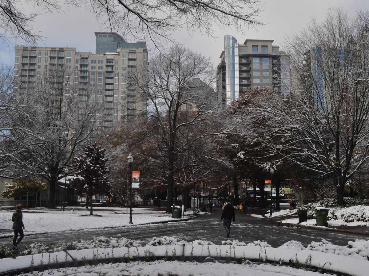 A park and tall glassy building covered in snow, with trees and joggers in the foreground.