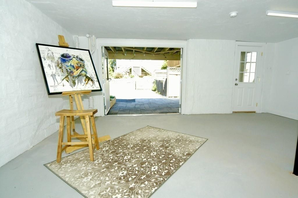 A garage with an open door, and it's empty other than a painting on an easel.