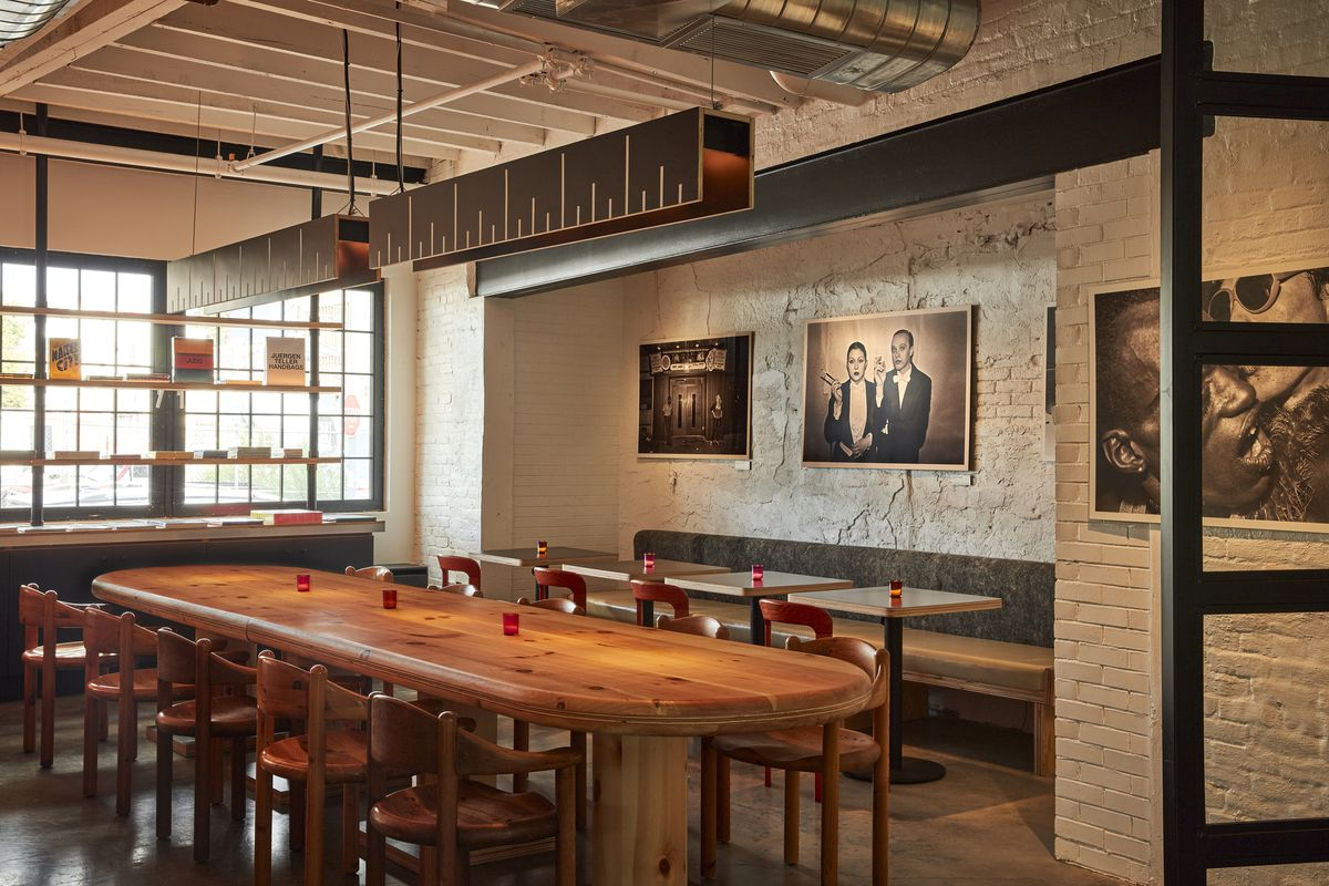 A dining room with a long wooden table and black and white photos on the white brick walls.
