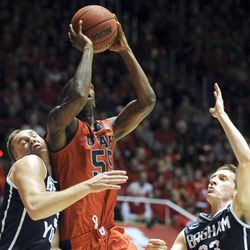 Utah Utes guard Delon Wright (55) draws the fouling going to the basket between Brigham Young Cougars guard Kyle Collinsworth (5) and Brigham Young Cougars guard Skyler Halford (23) during a game at the Jon M. Huntsman Center on Saturday, Dec. 14, 2013.