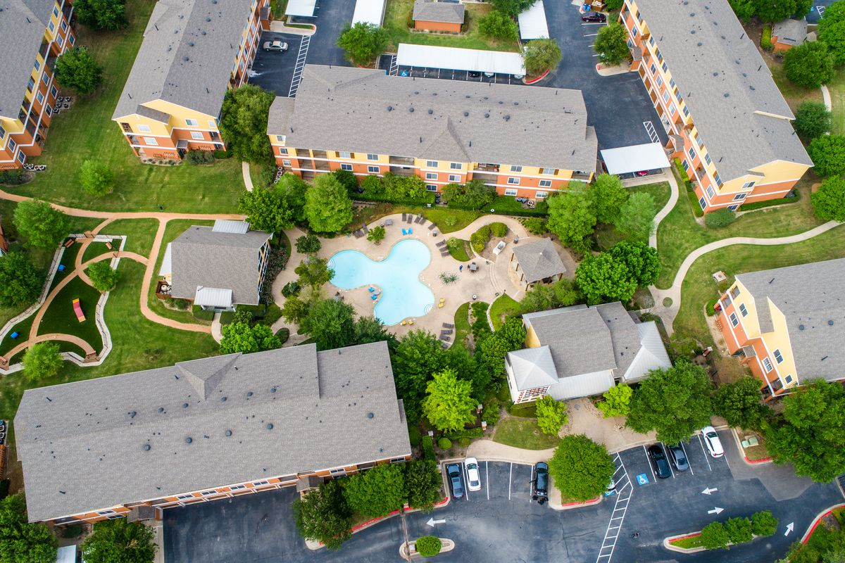 Aerial view of several multistory apartment buildings with a pool, a dog park, and other green space.