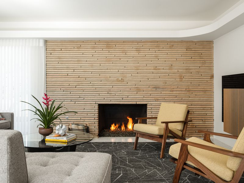 A living room has a large fireplace with a rug and seating around it.