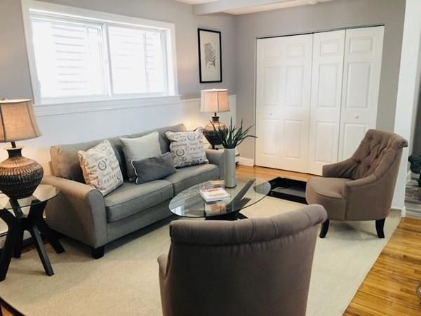 A contemporary living room with two chairs facing a couch on a rug.