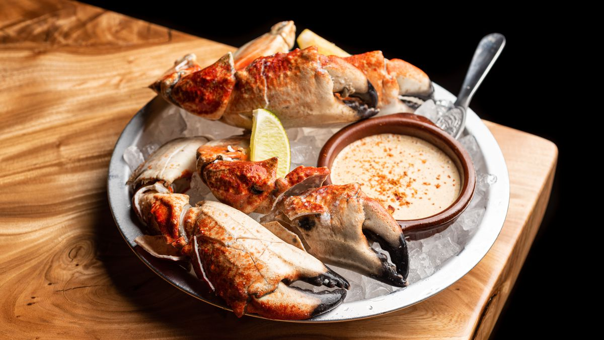 Stone crab claws over ice on a wooden table.