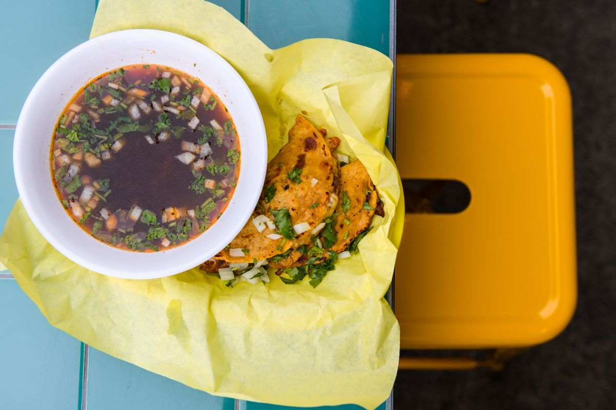 Birria at Papi Chulo's comes with two dorados tacos filled with meat, as well as a side bowl of stock with onions and cilantro