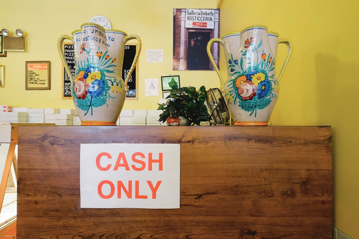 A cash only sign and two colorful vases covered with painted flowers on the wooden counter of Galleria Umberto in Boston's North End
