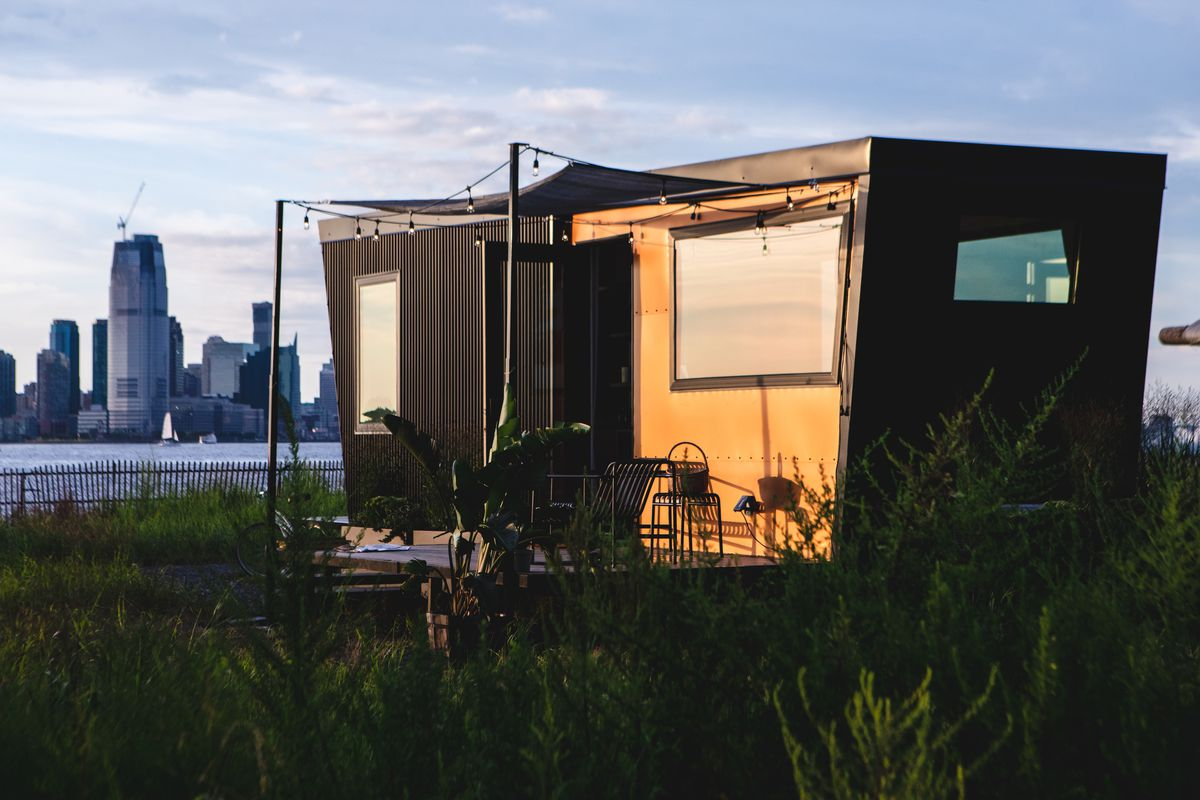 A tiny house with a private deck is parked on an island. Tall buildings are in the background.