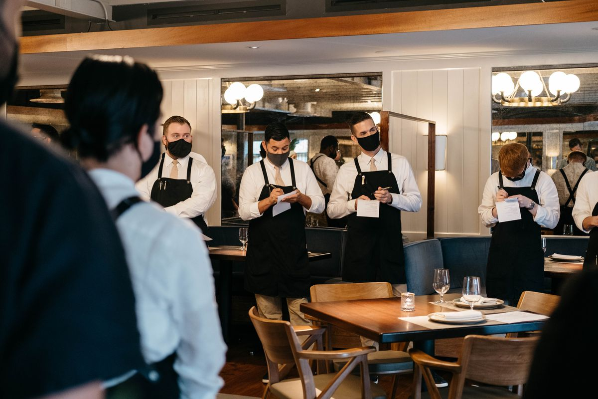 A group of restaurant servers, wearing beige ties, white shirts, and black aprons, stand in a brightly lit dining room taking notes.
