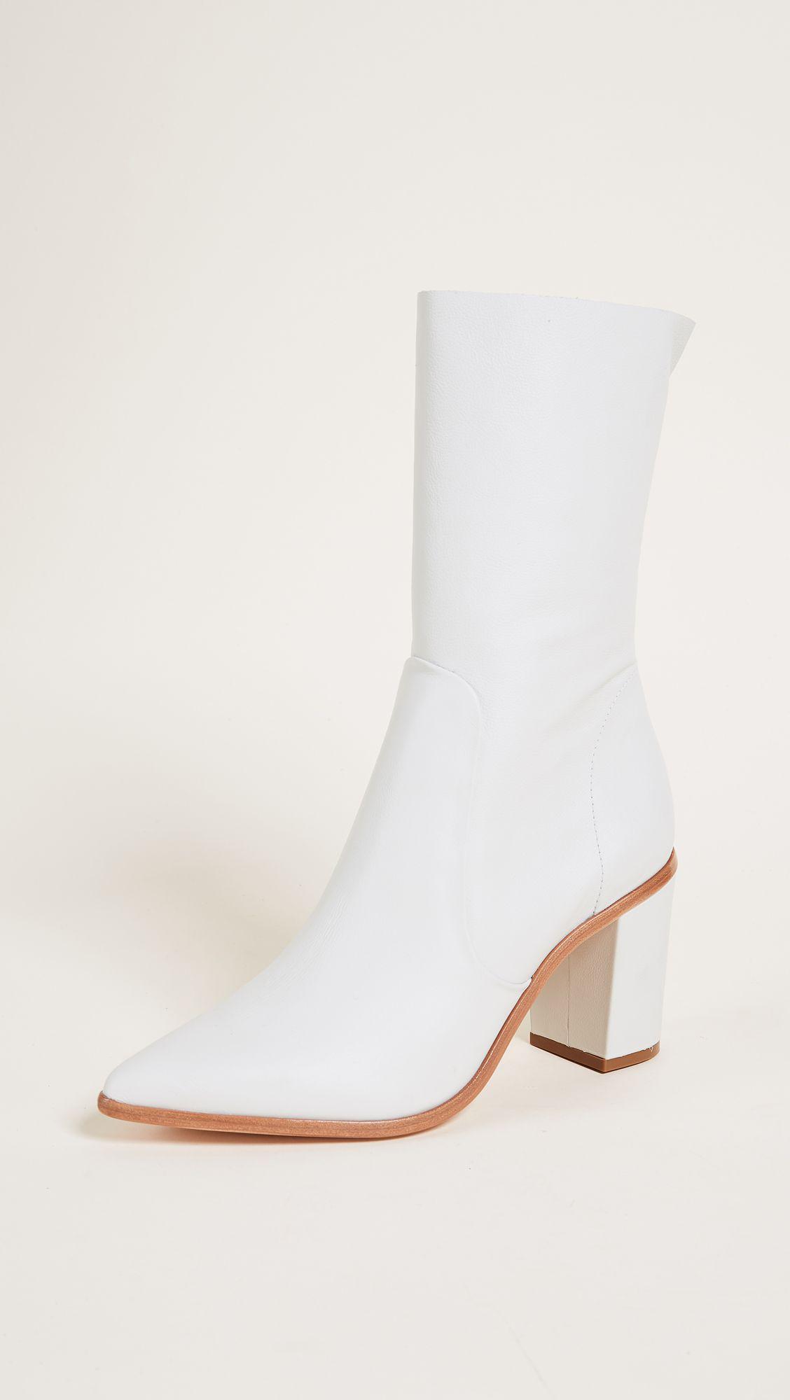 A pair of white Schutz boots