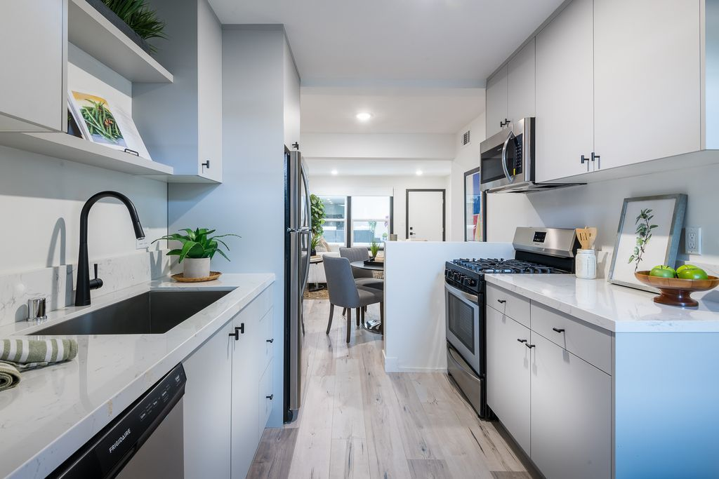 A galley kitchen with white countertops and stainless steel appliances