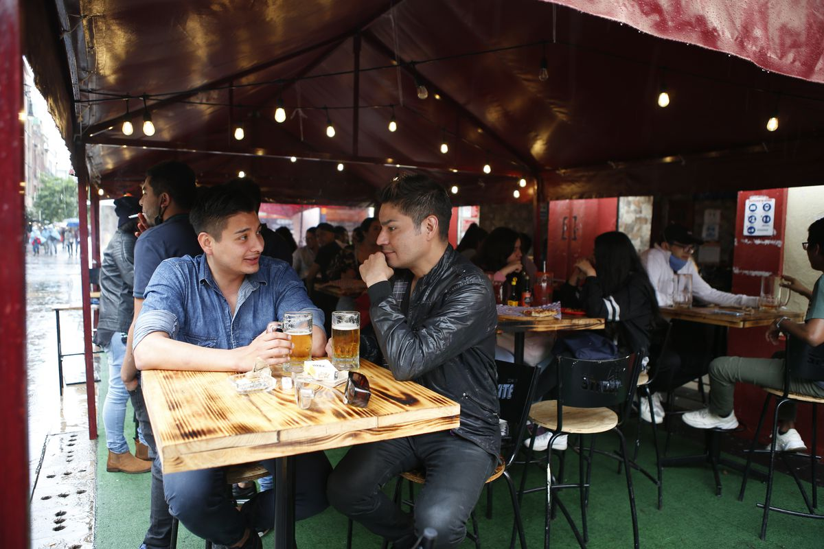 Luis Alvarez, 27 (left), and Pablo Quintero, 35, drink beer at a bar in Mexico City. Mexico is now in its third wave of the coronavirus pandemic. The country's health department says the growth is largely coming from infections among younger people.